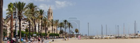 BARCELONA, SPAIN - APRIL 30, 2020: People on urban street with palm trees and Church of Saint Bartolomeus and Santa Tecla at background, panoramic crop