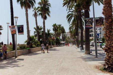 Photo pour CATALONIE, ESPAGNE - 30 AVRIL 2020 : Personnes marchant dans les rues urbaines près des palmiers - image libre de droit