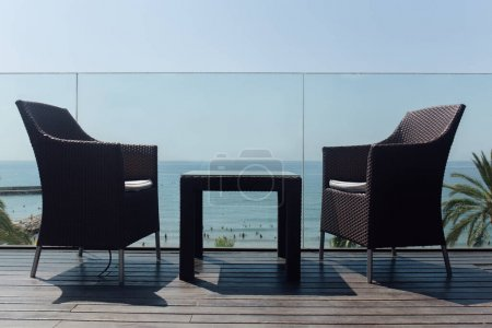 Low angle view of table and chairs near glass fencing and seascape at background in Catalonia, Spain