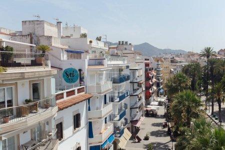 Photo pour CATALONIE, ESPAGNE - 30 AVRIL 2020 : Rue urbaine avec bâtiments, palmiers et montagnes avec ciel bleu en arrière-plan - image libre de droit
