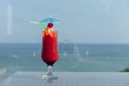 Photo pour Verre de cocktail avec parapluie et pailles à boire sur la table avec mer et ciel bleu à l'arrière-plan - image libre de droit
