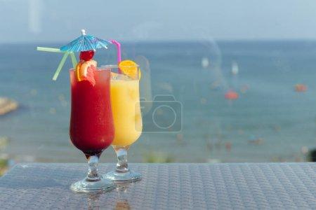 Photo pour Verres de cocktails sur table avec mer et ciel bleu à l'arrière-plan - image libre de droit