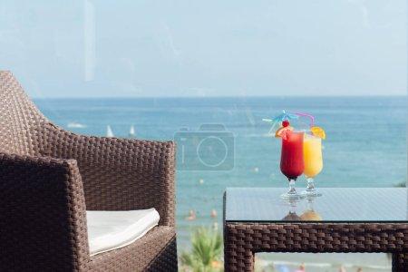 Photo pour Verres de cocktails sur la table près de la chaise avec paysage marin et ciel clair à l'arrière-plan - image libre de droit