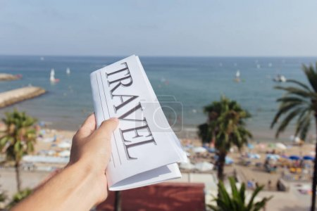 Photo for Cropped view of man holding newspaper with travel lettering on beach and blue sky at background - Royalty Free Image