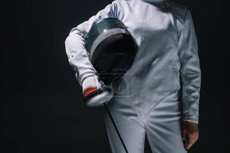 Vista recortada del esgrimista que sostiene la máscara de esgrima y el estoque aislados en negro