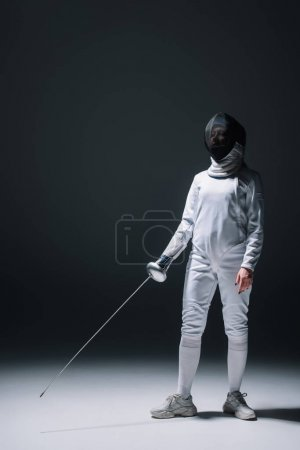 Photo pour Escrime dans le masque de clôture tenant rapière tout en se tenant sur la surface blanche sur fond noir - image libre de droit