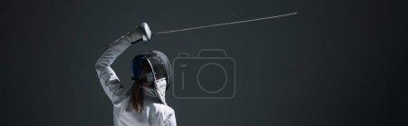 Photo pour Vue arrière de l'entraînement de l'escrimeur avec rapière isolée sur noir, culture panoramique - image libre de droit