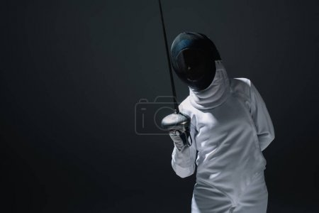 Swordswoman in fencing suit and mask holding rapier isolated on black