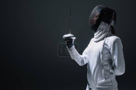 Photo pour Vue latérale de l'escrime dans le masque de clôture tenant rapière isolé sur noir - image libre de droit