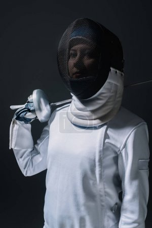 Fencer in fencing mask looking at camera and holding rapier isolated on black