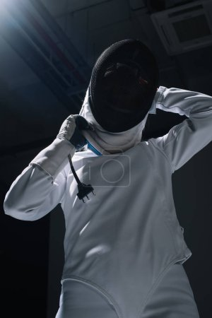 Low angle view of fencer putting on fencing mask