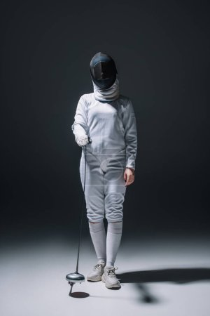 Photo for Fencer in fencing mask holding rapier on black background - Royalty Free Image
