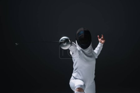 Fencer in fencing mask exercising with rapier isolated on black