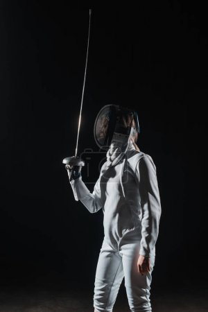 Photo for Fencer in fencing mask holding rapier isolated on black - Royalty Free Image