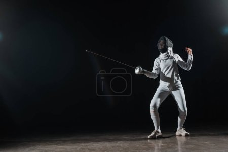 Fencer training with rapier under spotlight on black background
