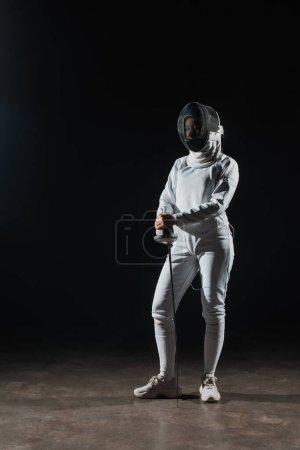 Photo pour Escrimeur en masque d'escrime et costume tenant rapière sur fond noir - image libre de droit