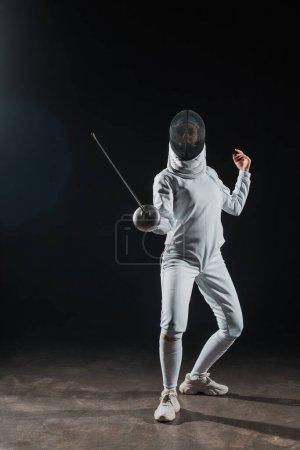 Photo pour Escrime dans le masque d'escrime tenant rapière tout en s'entraînant sous les projecteurs sur fond noir - image libre de droit