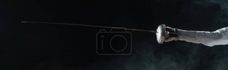 Photo for Panoramic orientation of fencer in glove holding rapier on black background with smoke - Royalty Free Image