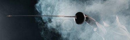 Photo pour Vue panoramique de l'escrime tenant rapière sur fond noir avec de la fumée - image libre de droit
