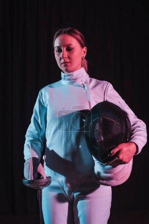 Photo pour Escrime attrayant tenant masque de clôture et rapière isolé sur noir - image libre de droit