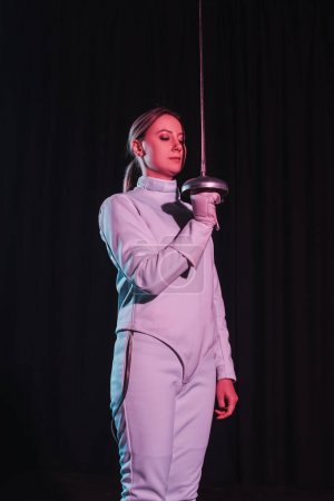 Photo for Beautiful woman in fencing suit holding rapier isolated on black - Royalty Free Image