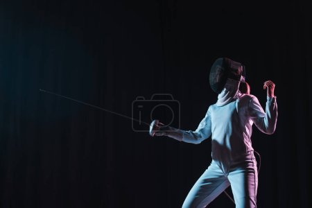 Swordswoman fencing with rapier isolated on black