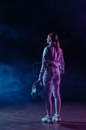 Photo for Back view of fencer holding fencing mask and rapier on black background with smoke - Royalty Free Image