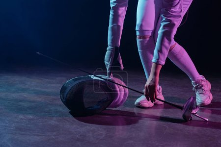 Photo for Cropped view of swordswoman putting fencing mask and rapier on floor on black background - Royalty Free Image