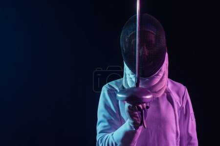 Fencer in fencing mask and glove holding rapier isolated on black