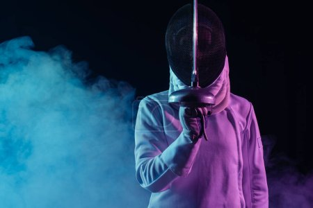 Photo for Swordswoman in fencing mask holding rapier on black background with smoke - Royalty Free Image