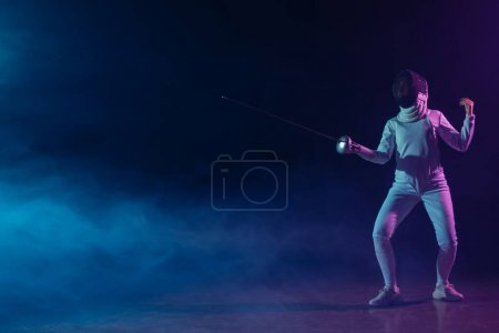 Photo for Swordswoman in fencing suit and mask holding rapier on black background with smoke and lighting - Royalty Free Image
