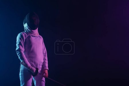 Fencer in fencing mask and suit holding rapier isolated on black