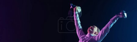 Photo for Excited and cheerful fencer holding rapier and fencing mask isolated on black, horizontal crop - Royalty Free Image