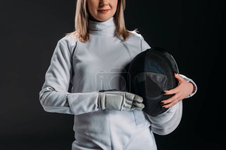 Photo for Cropped view of fencer holding fencing mask isolated on black - Royalty Free Image