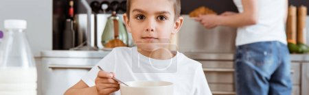 Panoramic crop of boy looking at camera while eating breakfast in kitchen