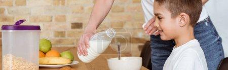 Photo pour Orientation panoramique de la mère versant du lait dans les céréales près du fils souriant à table dans la cuisine - image libre de droit