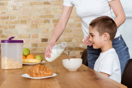 Mother pouring milk in bowl with cereals near smiling son at kitchen table