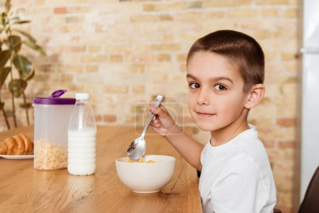 Photo for Side view of boy looking at camera while eating cereals in kitchen - Royalty Free Image