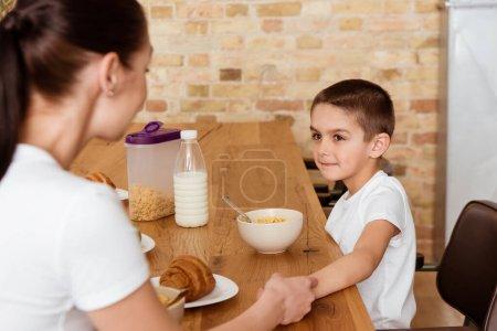 Photo pour Sélection du garçon et de la mère tenant la main près des céréales et des croissants sur la table de cuisine - image libre de droit