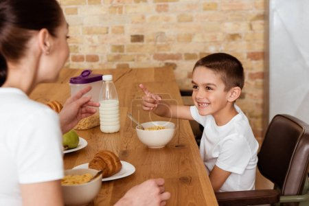 Photo pour Concentration sélective de l'enfant joyeux pointant du doigt la mère pendant le petit déjeuner dans la cuisine - image libre de droit