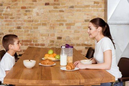 Photo pour Vue latérale d'une mère souriante regardant son fils près des céréales et des croissants sur la table de la cuisine - image libre de droit