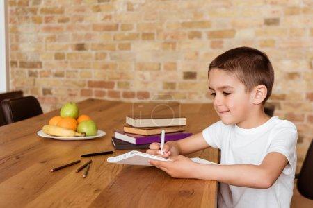 Photo pour Garçon écrit sur copybook près des livres et crayons sur la table - image libre de droit