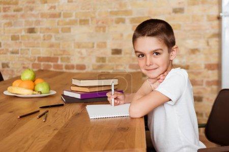 Photo pour Vue latérale de l'enfant regardant la caméra tout en écrivant sur le carnet près des livres et des fruits sur la table - image libre de droit