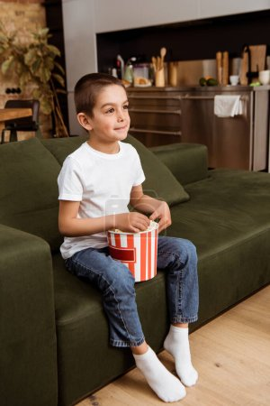 Kid holding bucket of popcorn while watching movie on couch