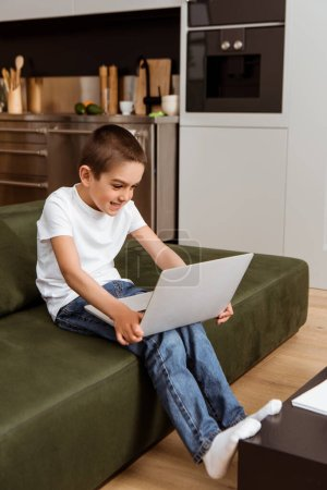 Selective focus of smiling boy using laptop on couch at home