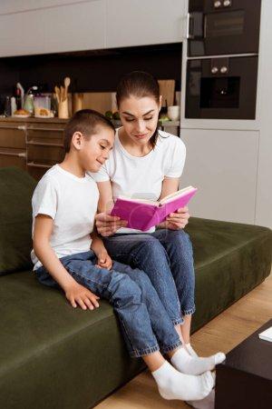 Photo pour Concentration sélective de la mère et du fils souriant lisant le livre sur le canapé - image libre de droit