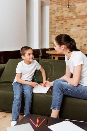 Photo pour Foyer sélectif de sourire garçon regardant la mère tout en dessinant avec crayon de couleur sur le canapé - image libre de droit