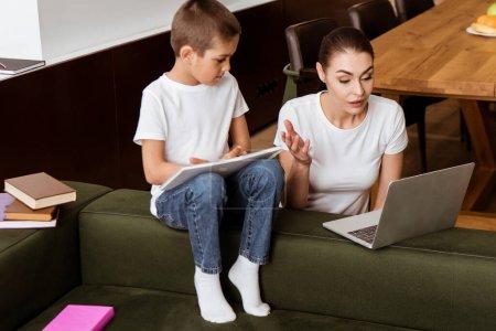 Photo pour Mère regardant ordinateur portable près du fils avec du papier et des livres sur le canapé dans le salon - image libre de droit