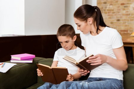 Photo for Mother and son reading books near paper and color pencils on couch - Royalty Free Image