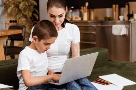 Photo for Selective focus of boy using laptop during online education near mother, color pencils and paper on couch - Royalty Free Image